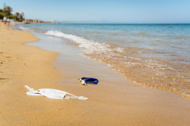 Strand vervuild met gezichtsmaskers van covid. milieuverontreinigingsprobleem