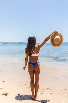 Strand zomervakantie vrouw in gelukkig vrijheid concept met uitgestrekte armen. latijnse sexy vrouw die witte bikini met strohoed in handen draagt