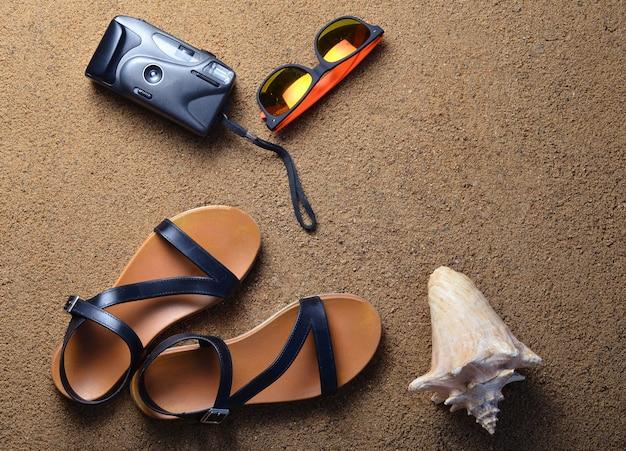 Strandaccessoires liggen op het zand. camera, sandalen, zonnebril, schelpen. het concept van ontspannen op zee. het zomerse strandseizoen is open! bovenaanzicht