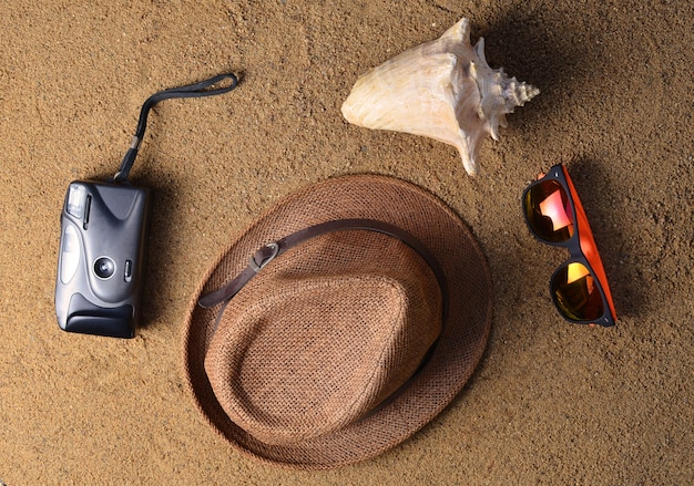 Strandaccessoires liggen op het zand. hoed, camera, zonnebril, schelp. het concept van ontspannen op zee. het zomerse strandseizoen is open! bovenaanzicht