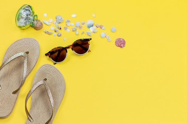 Strandaccessoires met kopie ruimte. zonnebrillen, slippers en schelpen