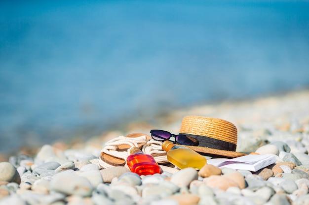 Strandaccessoires strooien hoed boek zonnebril en flip flop op het strand