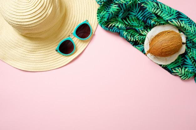 Strandaccessoires voor dames: strohoed, zonnebril, kokosnoot, groene sjaal op roze achtergrond. het concept van het reizigersmateriaal, de zomerachtergrond met exemplaarruimte.