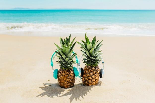 Strandachtergrond met ananassen die hoofdtelefoons dragen