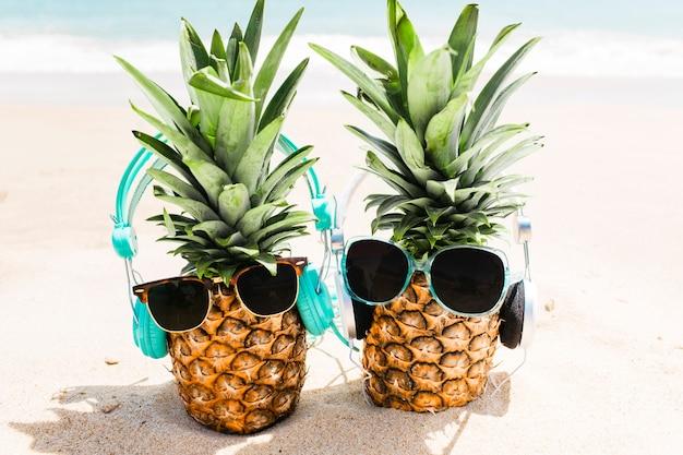 Strandachtergrond met ananassen die hoofdtelefoons en zonnebril dragen