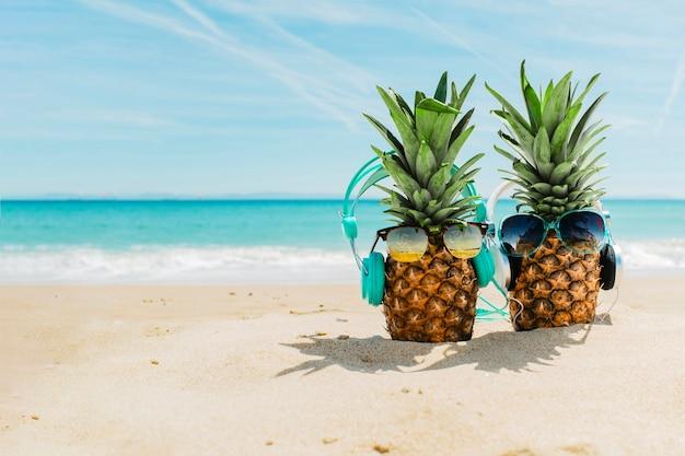 Strandachtergrond met koele ananassen die hoofdtelefoons dragen