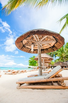 Strandbedden en parasols op exotisch tropisch wit zandstrand