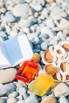 Strandhoed op geopend boek met zonnebrandcrème en schoenen op kiezelstrand