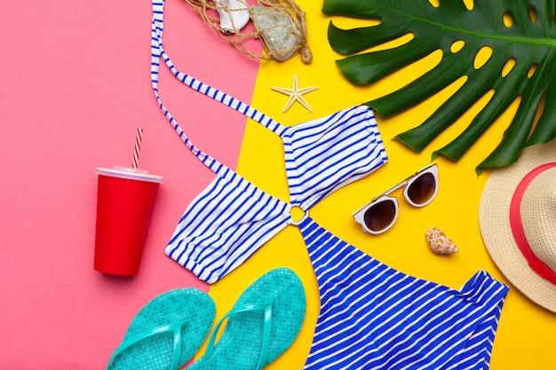 Strandkleding en accessoires op een roze en gele achtergrond