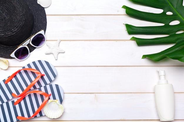 Strandkleding en accessoires op een witte houten achtergrond