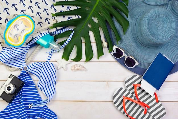 Strandkleding en accessoires op een witte houten