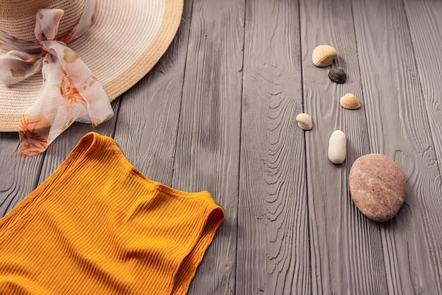 Strandkleding oranje vrouw top outfit hoed tas zonbescherming zonnebril kiezelstenen. zomer achtergrond