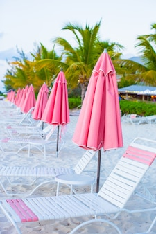 Strandlounges onder een paraplu op wit zand