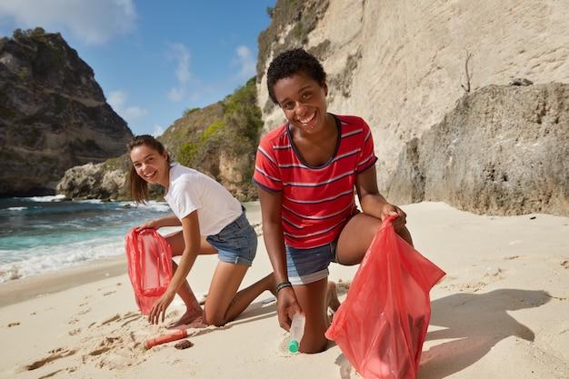Strandomgeving en afvalconcept opruimen. twee vrolijke vrijwilligers halen afval op aan de kust