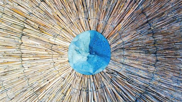 Strandparasol van riet met metalen dop aan de bovenzijde