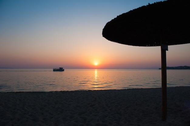 Strandparasols bij zonsondergang, met ligbedden, hete zonsondergang. zachte zee golven en bubbels op het strand met avondrood. varende boot bij zonsondergang dichtbij het strand, strandparaplu