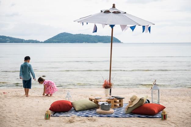 Strandpicknick met champagne en eten onder parasol terwijl kinderen met het zand spelen