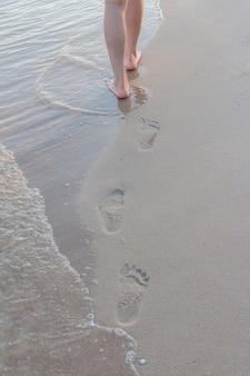 Strandreis alleen - vrouw die alleen op zandstrand loopt dat voetafdrukken in het zand verlaat het detail van de close-up