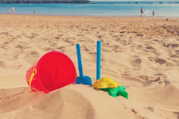 Strandspeelgoed in zand aan de kust op zonnige zomerdag, retro afgezwakt