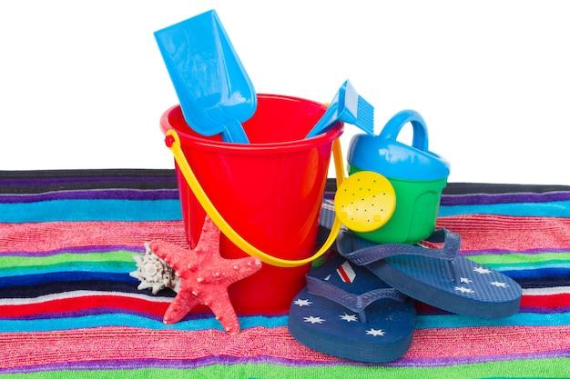 Strandspeelgoed met slippers en zeester op handdoek geïsoleerd op een witte achtergrond