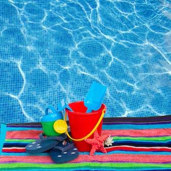 Strandspeelgoed met slippers en zeester op handdoek