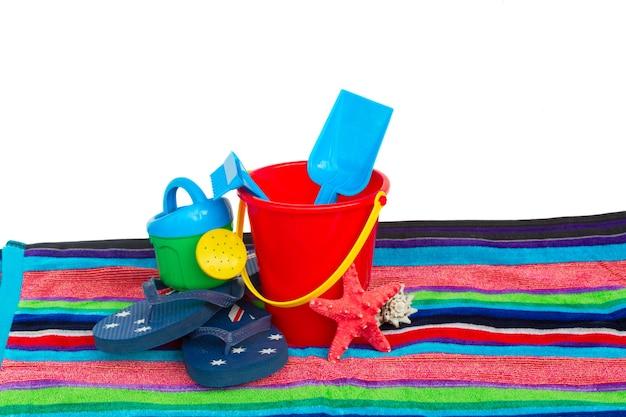 Strandspeelgoed met slippers op handdoek geïsoleerd op witte achtergrond
