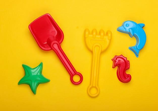 Strandspeelgoed voor kinderen, of zandbakspeelgoed op een geel
