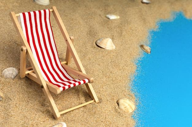 Strandstoel in het zand met schelpen
