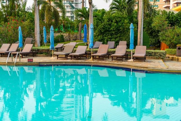 Strandstoel of zwembadbed met parasol rond het zwembad bij zonsondergang