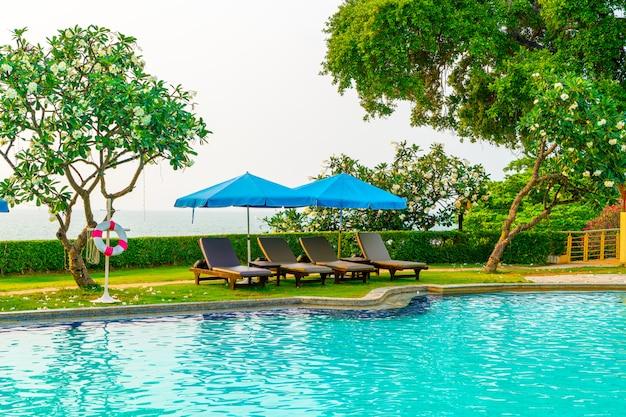Strandstoel of zwembadbed met parasol rond zwembad met zonsondergang en zee