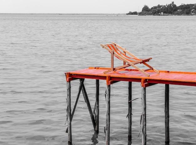 Strandstoel op het ponton naast de oceaan
