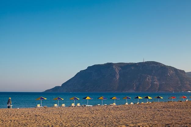 Strandstoelen en parasols op het strand van het eiland kos