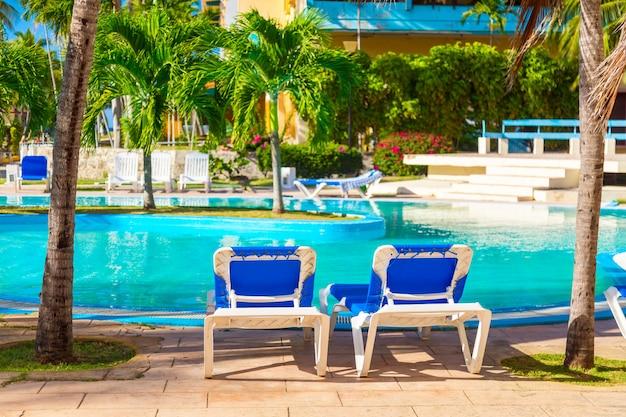 Strandstoelen in de buurt van zwembad in tropische resort met palmbomen.