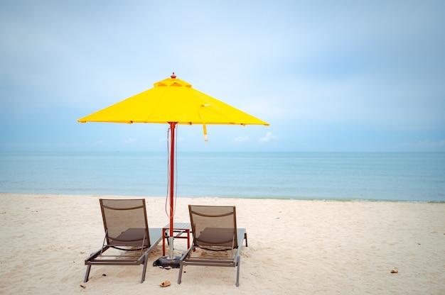 Strandstoelen onder een gele paraplu op strand met zachte blauwe hemel
