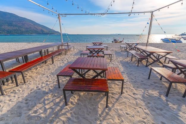 Strandstoelen, parasol en palmen op het prachtige strand voor vakantie en ontspanning op koh lipe eiland, thailand