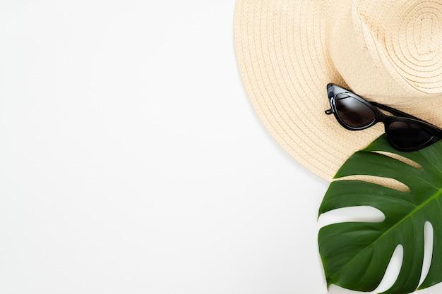 Strandstrohoed, zonnebril en tropisch monstera-palmblad op witte achtergrond
