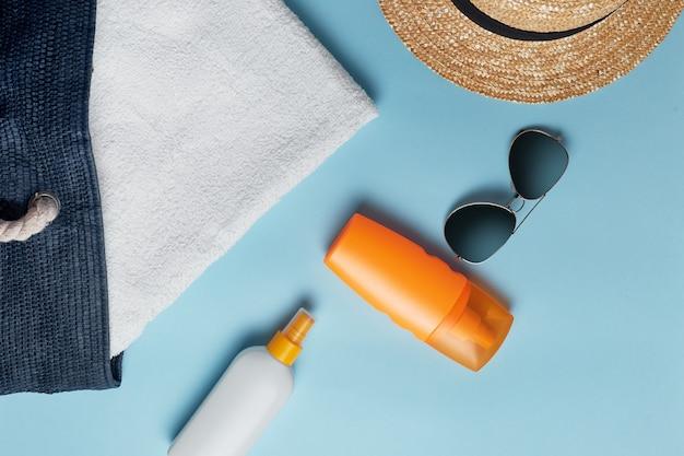 Strandtas met strandaccessoires op een bovenaanzicht van een gekleurde achtergrond. zonnebrandcrème, handdoek, bril, hoed.
