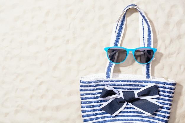 Strandtas met zonnebril op het zand. bovenaanzicht