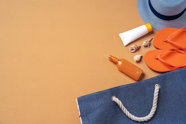 Strandtas met zonneproducten, slippers en hoed op beige