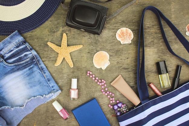 Strandtas, zonnehoed, cosmetica, denim shorts, camera, schelpen op oude houten achtergrond.