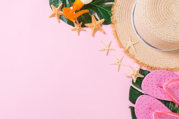 Strandtoebehoren met strohoed, zonneschermfles en seastar op roze hoogste mening als achtergrond met exemplaarruimte