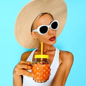 Strandvakantie stemming. glamoureuze blonde met frisse cocktail. strandfeestlook