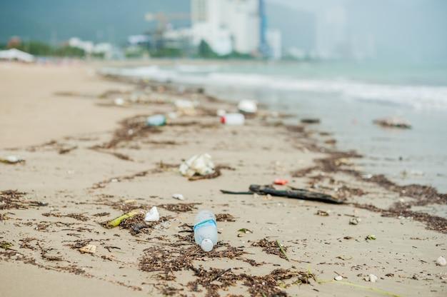 Strandvervuiling. plastic flessen en ander afval op zee strand