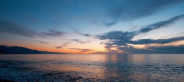 Strandzonsondergang met eindeloze horizon en kalme golven de bergen in de verte