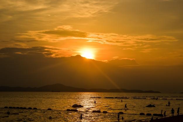 Strandzonsondergang met zandige silhouetmensen