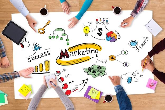 Strategie bespreken. bovenaanzicht van papier met kleurrijke schetsen op de houten tafel en mensen die eromheen zitten