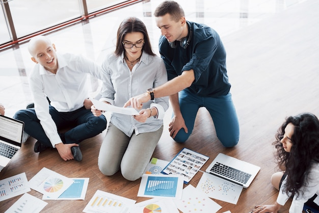 Strategie samen plannen. commercieel team die documenten op vloer met manager bekijken die aan één idee richten. samenwerking bedrijfsprestaties. planning ontwerp tekenen. teamwerk concept