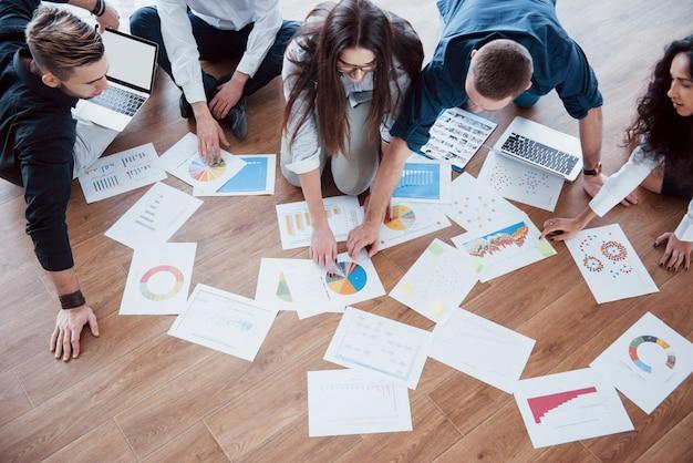 Strategie samen plannen. commercieel team die documenten op vloer met manager bekijken die aan één idee richten.