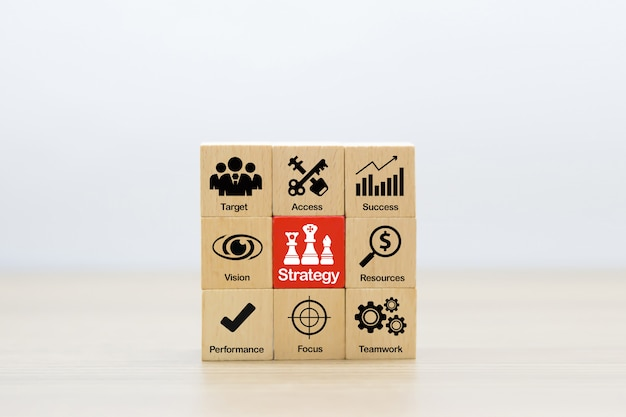 Strategiepictogrammen op houten blok voor succes, prestaties, beheer en bedrijfsgroei.