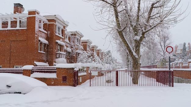 Straten en gebouwen bedekt met sneeuw overdag als gevolg van sneeuwstorm filomena die valt in madrid, spanje. europa
